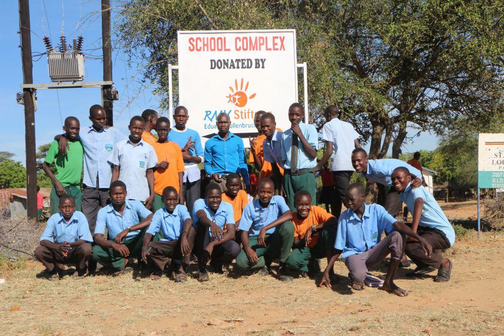 """Eine Gruppe glücklicher Schüler vor dem Schild """"School Complex donated bei RMV Stiftung Eduard Müllenbruch"""" in Uganda"""