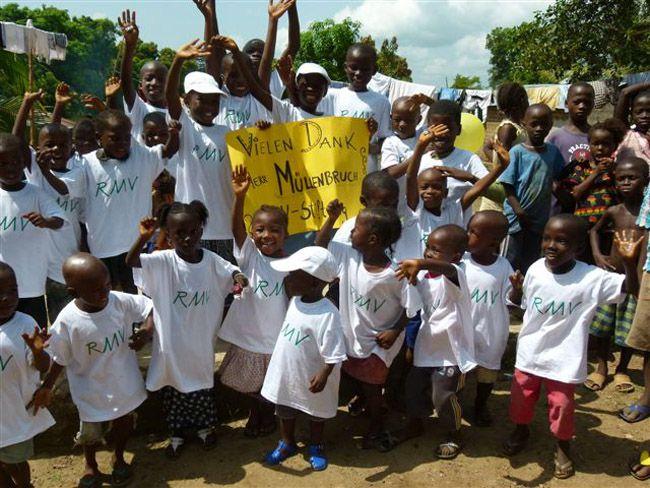 """Gruppenbild von Kindern im weißen RMV T-Shirt und gelbem Schild mit der Aufschrift """"Vielen Dank Herr Müllenbruch"""""""